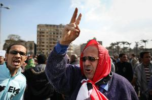CAIRO, EGYPT - JANUARY 30:  A man wrapped in an Egyptian flag gestures in Tahrir Square  on January 30, 2011 in Cairo, Egypt. As President Mubarak struggles to regain control after five days of protests he has appointed Omar Suleiman as vice-president. The present death toll stands at 100 and up to 2,000 people are thought to have been injured during the clashes which started last Tuesday. Overnight it was reported that thousands of inmates from the Wadi Naturn prison had escaped and that Egyptians were forming vigilante groups in order to protect their homes after Police were nowhere to be seen on the streets. Broadcasts from the Al-Jazeera television network via an Egyptian satellite have now been halted.  (Photo by Peter Macdiarmid/Getty Images)