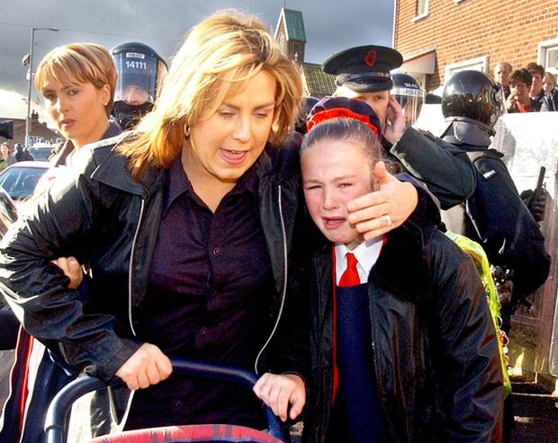 Catholic Holy Cross Primary School children in tears as their parents march them through armed police and army lines who where holding back protesting protestant residents in Ardoyne, North Belfast, on their first day back to school this morning.