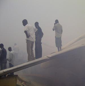 Onlookers stand on the tail wing of a crashed passenger plane near Murtala Muhammed International Airport in Lagos, Nigeria (AP)