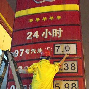 A worker changes the price board at a petrol station in in China's Sichuan province