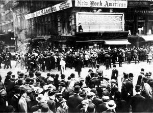 Crowds gather around the bulletin board of the New York American newspaper in New York, where the names of people rescued from the sinking Titanic are displayed.