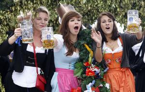 Young women wave with their beer steins while riding a decorated coach to the opening of the famous Oktoberfest beer festival in Munich, southern Germany, Saturday, Sept. 19, 2009. Some six million visitors from around the globe are expected to come to the Bavarian capital, until the end of the world famous beer festival on Oct. 4, 2009. (AP Photo/Matthias Schrader)