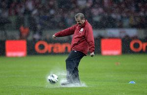 England manager Roy Hodgson tests the condition of the pitch in the pouring rain before the World Cup Group H Qualifying match at the National Stadium, Warsaw, Poland