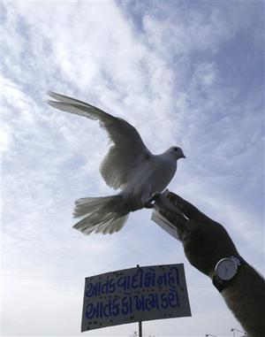 "An Indian Muslim, only hand seen, releases a pigeon during a protest against terrorist attacks in Mumbai, as a placard reads "" Kill terror not terrorist "" in Ahmadabad, India, Saturday, Nov. 29, 2008. Indian commandos killed the last remaining gunmen holed up at a luxury Mumbai hotel Saturday, ending a 60-hour rampage through India's financial capital by suspected Islamic militants that killed people and rocked the nation. (AP Photo/Ajit Solanki)"