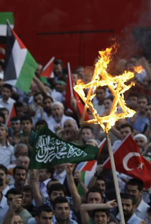 Protesters burn a Star of David during a demonstration outside the Israeli consulate in Istanbul, Monday, May 31, 2010
