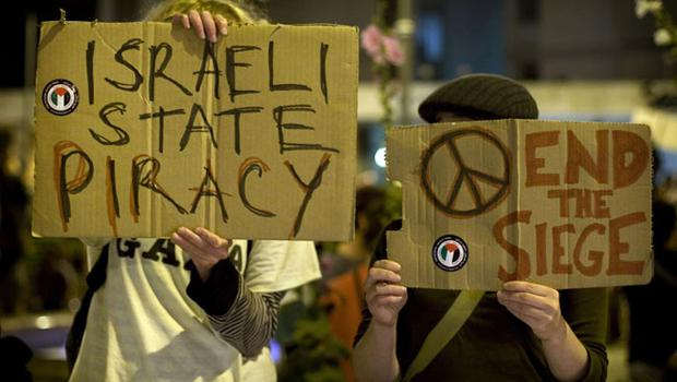 Israeli and foreign left-wing protestors hold placards against Israeli policies during a protest against Israeli naval commandos raid on a flotilla