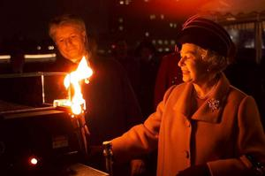 31/12/1999 Queen Elizabeth II lights a beacon floating in the Thames as she travels by boat to the Millennium Dome at Greenwich. PRESS ASSOCIATION Photo.