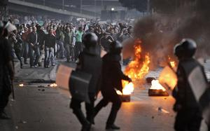 Egyptian riot police clash with anti-government activists in Cairo, Egypt, Wednesday, Jan. 26, 2011.  Egyptian anti-government activists clashed with police for a second day Wednesday in defiance of an official ban on any protests but beefed up police forces on the streets quickly moved in and used tear gas and beatings to disperse demonstrations. (AP Photo/Ben Curtis)