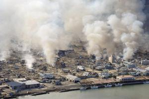 White smokes rise from still burning house in Yamadamachi in Iwate Prefecture (state), northern Japan, Saturday, March 12, 2011, one day after a strong earthquake-triggered devastating tsunami hit the area