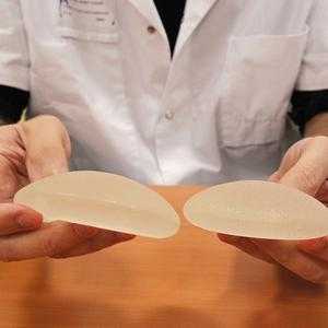 A plastic surgeon holds silicone implants removed from a patient because of concerns that they are unsafe (AP)