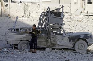 A Palestinian boy stands next to a destroyed car after an Israeli airstrike in the Jabaliya refugee camp, northern Gaza Strip, Sunday, Nov. 18, 2012. The Israeli military widened its range of targets in the Gaza Strip on Sunday to include the media operations of the Palestinian territory's Hamas rulers, sending its aircraft to attack two buildings used by both Hamas and foreign media outlets. (AP Photo/Hatem Moussa)