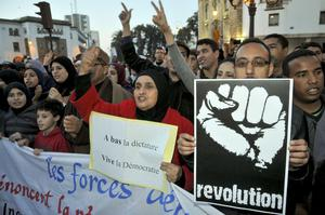 Moroccan people gather to show their solidarity with the Egyptian protesters, following the resignation of President Hosni Mubarak, during a protest in Rabat, Morocco, on Friday, Feb. 11, 2011. At centre women hold banner which reads ''Knock down dictator, hurray democracy''