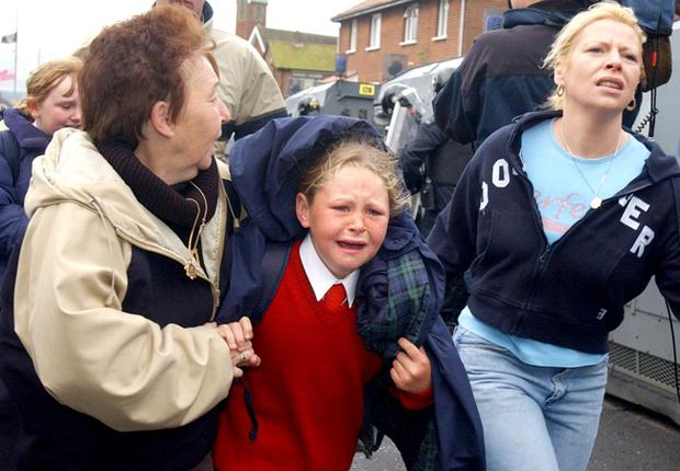 Terrified school children after a blast bomb was launched by protesting loyalists. The blast bomb injured one policeman and a police dog, this is the third morning trouble has flared as catholic parents and their children through a protestant area to the Holy Cross Primary School in Ardoyne, North Belfast.