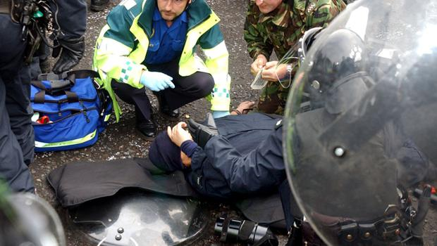 An injured police officer is helped into an ambulance by his colleagues after a blast bomb was thrown at them from protesting loyalists in the Glenbryn area of Ardoyne, North Belfast, this morning, this is the third morning trouble has flared as catholic parents and their children through a protestant area to the Holy Cross Primary School in Ardoyne, North Belfast.