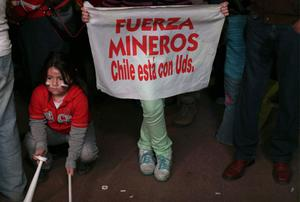 """A person holds a sign that reads in Spanish """"Strength miners, Chile is with you"""" with a group of people watching on rescue operations on TV taking place at the San Jose mine to free 33 trapped miners, in Copiapo, Chile, late Tuesday Oct. 12, 2010.  Thirty-three miners became trapped when the gold and copper mine collapsed on Aug. 5. (AP Photo/Dario Lopez-Mills)"""