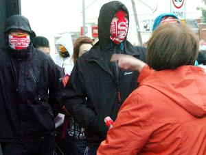 Angry confrontation between a local woman and masked youths at  Ardoyne shops on a fourth consecutive night of rioting July 2010