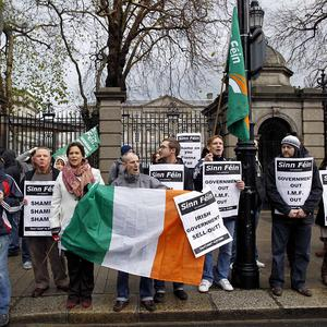 Sinn Fein protesters demonstrate outside Leinster House over the government's handling of the economic crisis (AP)