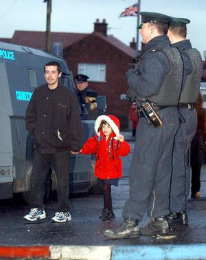 Security forces keep a watchful eye as a young girl and her father walk up the Ardoyne Road in North Belfast to Holy Cross school. Police stepped up their security outside North Belfast schools after recent threats and trouble as parents walked their children to school.