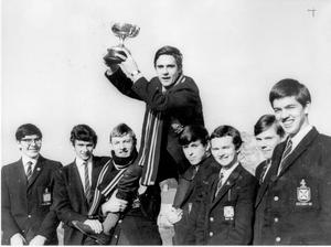 "Methodist College ""A"" team chair their captain Ken Shaw, after they had won the Northern Ireland schools' cross country championship, at Barnetts Park, Belfast. Also, included are Alan Bell, David Green, Rodney Stone, Michael Stevenson, Michael McKimm, Brian Rowe and Eric McKee. The cup was presented by the ""Belfast Telegraph."" 1969."
