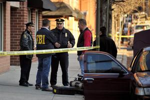HOBOKEN, NJ - DECEMBER 14:  Hoboken Police Department Captain James Fitzsimmons (C) speaks with other law enforcement including FBI at a scene at 1313 Grand St., which is believed to be connected with an elementary school shooting on December 14, 2012 in Hoboken, New Jersey. According to reports, there are 27 dead, including 20 children, after a gunman identified as Adam Lanza, opened fire in at the Sandy Hook Elementary School in Newtown, Connecticut. The shooter, identified as Adam Lanza was also found dead at the scene.  (Photo by Michael Bocchieri/Getty Images)