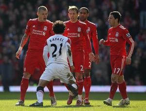 LIVERPOOL, ENGLAND - MARCH 06:  Rafael of Manchester United is confronted by Martin Skrtel (L) and Lucas of Liverpool during the Barclays Premier League match between Liverpool and Manchester United at Anfield on March 6, 2011 in Liverpool, England.  (Photo by Alex Livesey/Getty Images)