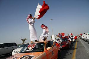 MANAMA, BAHRAIN - FEBRUARY 18:  Pro-government demonstrators ride atop cars during a show of support for the monarchy on February 18, 2011 in Manama, Bahrain. Anti-government protesters were fired at with live ammunitions, with protesters saying it was followed by teargas, which drove the demonstrators back. There are unconfirmed reports that there are four dead in the clashes.  (Photo by John Moore/Getty Images)