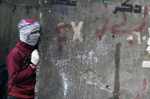A protester covers his face as he looks from behind a wall at Egyptian riot police, unseen, during clashes near Tahrir Square in Cairo, Egypt, Monday, Nov. 21, 2011. Security forces fired tear gas and clashed Monday with several thousand protesters in Cairo's Tahrir Square in the third straight day of violence that has killed at least two dozen people and has turned into the most sustained challenge yet to the rule of Egypt's military.(AP Photo/Khalil Hamra)