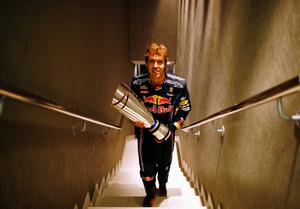ABU DHABI, UNITED ARAB EMIRATES - NOVEMBER 14:  Race winner and F1 2010 World Champion Sebastian Vettel of Germany and Red Bull Racing carries his winners trophy back to his changing room following the Abu Dhabi Formula One Grand Prix at the Yas Marina Circuit on November 14, 2010 in Abu Dhabi, United Arab Emirates.  (Photo by Mark Thompson/Getty Images)