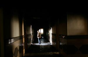 CAIRO, EGYPT - JANUARY 30:  A man stands in the charred hallway of a burned government building January 30, 2011 in Cairo, Egypt. Cairo remained in a state of flux and marchers continued to protest in the streets and defy curfew, demanding the resignation of Egyptian president Hosni Mubarek. As President Mubarak struggles to regain control after five days of protests he has appointed Omar Suleiman as vice-president. The present death toll stands at 100 and up to 2,000 people are thought to have been injured during the clashes which started last Tuesday. Overnight it was reported that thousands of inmates from the Wadi Naturn prison had escaped and that Egyptians were forming vigilante groups in order to protect their homes.   (Photo by Chris Hondros/Getty Images)