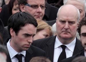 Funeral of Cork plane crash victim Brendan McAleese takes place at St MacNissus church in Tannaghmore, Co Antrim.  Crash survivors Donal Walsh (left) and  Laurence Wilson (right) follow Brendan McAleese's coffin out of the church after the service.