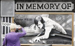 A woman taking a picture of a new mural of Alex Higgins at the Royal Bar on Belfast's Donegal Road. August 2010