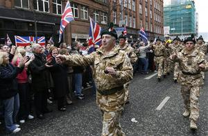 Supporters cheer the British Army's Royal Irish Regiment as it parades through Belfast city under tight security from riot police, in Belfast, Northern Ireland, Sunday, Nov. 2, 2008.  Riot police kept apart rival loyalist and Republican supporters at a parade to honor Northern Ireland members of British armed forces that have recently returned from war zones in Iraq and Afghanistan.  (AP Photo/Peter Morrison)