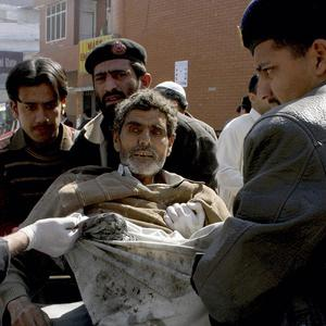 Hospital staff help a man injured in a suicide attack that killed more than 30 people at a funeral (AP)