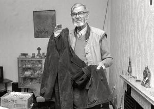 JAMES WRAY IN HIS HOME IN THE BOGSIDE DERRY HOLDING THE COAT WITH BULLIET HOLES IN THAT  HIS SON ALSO CALLED JAMES WRAY WAS KILLED ON BLOODY SUNDAY