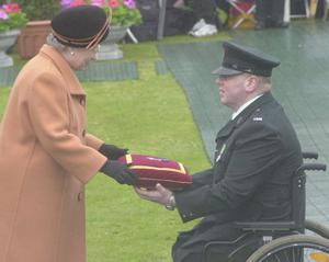 Her Majesty the Queen presents the George Cross to Constable Paul Slaine, who lost both legs in am IRA attack in 1992. April 2000Picture by Mervyn Dowling
