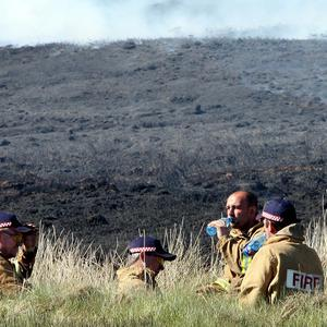 Firefighters take a rest from trying to contain a gorse fire in North Antrim, near Ballypatrick forest