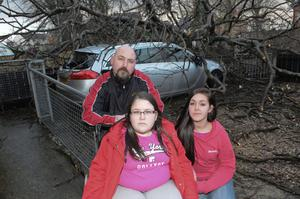 Mark Hamilton whose car was badly damaged when a tree fell early on Tuesday morning pictured with his daughters Katlin and Shannenoutside the family home in Broomhill Avenue in Londonderry's Waterside