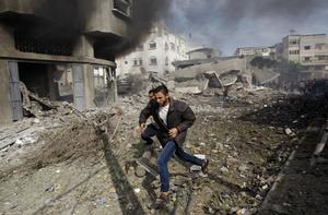 Palestinians run away from a damaged building after an Israeli air strike in Gaza City, Sunday, Nov. 18, 2012. Israel widened the range of targets in its Gaza offensive Sunday, striking more than a dozen homes of suspected Hamas militants and two media offices, according to security officials and witnesses. The attacks also damaged adjacent houses, killing seven civilians, including five children, health officials said.  (AP Photo/Adel Hana)