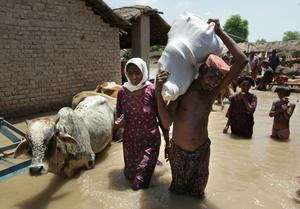 Pakistani flood victims get evacuated by the Pakistan Navy on a boat rescue mission as flood waters continue to rise