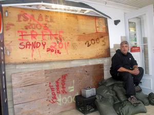 """Mark Palazzolo, owner of a bait and tackle shop on the Manasquan Inlet in Point Pleasant Beach, N.J., sits next to wood he has used to board up his business in previous major storms, Sunday, Oct. 28, 2012, in Point Pleasant Beach, N.J. Of Hurricane Sandy, he said, """"I think this is going to do us in."""" (AP Photo/Wayne Parry)"""