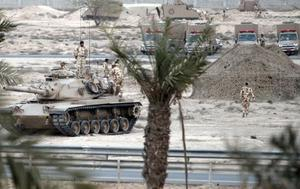 Bahraini soldiers in tanks and armoured vehicles stand ready  near a main road west of the capital Manama.