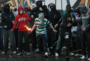 Youths clash with riot police before a loyalist band parade passes the Ardoyne shops