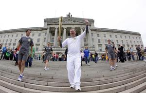 Press Eye - Belfast Northern Ireland - Sunday 3rd June 2012 - London 2012 Olympic Torch Relay Sports Minister Carl N Chuiln welcomes the Olympic Torch to Parliament Buildings this morning as part of the all-Ireland Torch Relay at Titanic Belfast this morning.Torch bearer John McAlpine from Newtownabbey leaves Stormont.Picture by Kelvin Boyes / Press Eye.