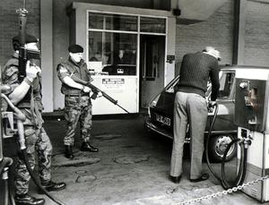 Soldiers stand guard as a Ministry of Commerce worker serves petrol at one of the Belfast City centre filling stations. Only essential users were being supplied. Ulster Workers Council Strike May 1974