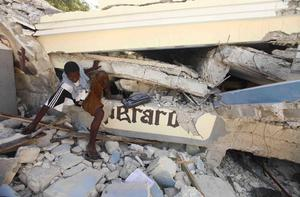 A man looks through the collapsed rubble of St. Gerard Church and School in Port-au-Prince,  Thursday, Jan. 14, 2010