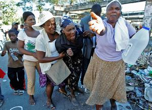 A group of women react in disbelief as the body of the daughter of a woman, at center, is missing after the earthquake, in Port-au-Prince