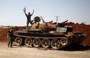 In this Monday, Aug. 6, 2012 photo, a Free Syrian Army fighter waves from the top of a destroyed army tank in the town of Anadan on the outskirts of Aleppo, Syria. (AP Photo/Khalil Hamra)