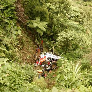 Rescuers and paramedics tend to passenger victims after a bus plunged off a Philippine mountain highway (AP)