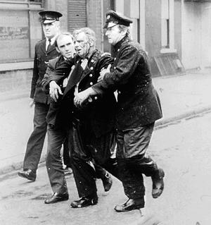 Belfast Fire Brigade Station officer McCleery, being carried from a bomb explosion, Cromac Street, circa 1971.