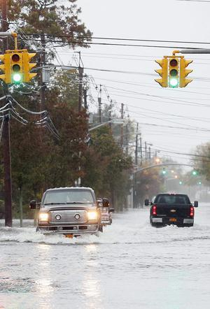 People make their way up a flooded Guy Lomardo Avenue as high tide and winds from Hurricane Sandy combine to flood the area on October 29, 2012 in Freeport, New York.